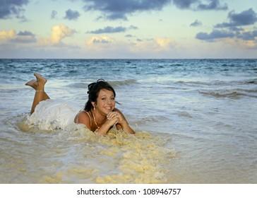 """A young woman """"trashing"""" her wedding dress in Hawaiian waters."""