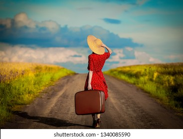 Young woman with travel siutcase on countryside road
