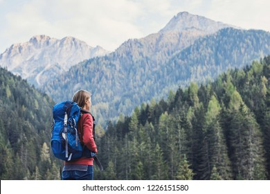 Young woman traveler in Alps mountains. Travel and active lifestyle concept. Traveler girl with backpack enjoying nature