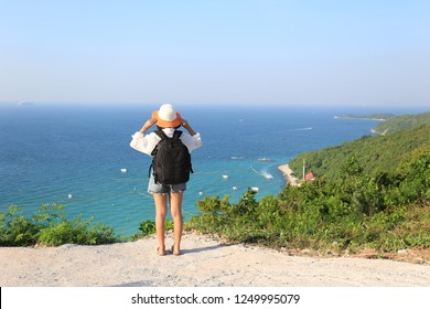 Young woman traveler with backpack enjoying and standing on mountains of the sea background, Koh Larn in Pattaya city, Chonburi Thailand