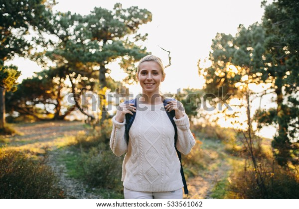 young woman traveler with backpack in the forest
