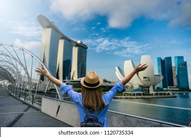 Young woman traveler with backpack and hat traveling into singapore city downtown. Travelling in Singapore concept