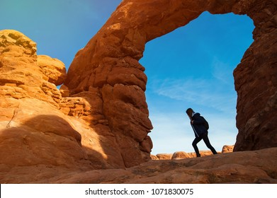 Young woman traveler with backpack  hiking the Turret Arch, Arches National Park in Utah