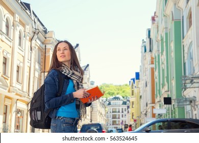 Young woman traveler with a backpack on her shoulder. Independent travel and out sightseeing in a history city. Student woman, her vacation. Learning foreign languages in a different country. Travel.