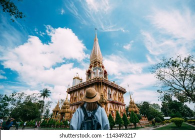 Young woman traveler with backpack traveling into beautiful pagoda in Wat Chalong or Chalong temple at Phuket town, Thailand. It's most popular thai temple in Phuket Thailand.