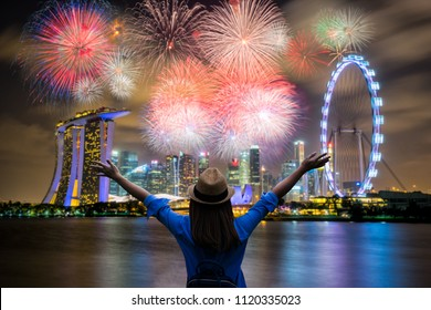 Young woman traveler celebrate and looking view of Singapore city landmark financial district at twilight sunset scene with multicolor firework celebration. Singapore city in national day celebration.