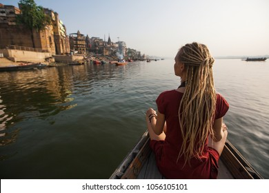 Young woman traveler with dreadlocks, on a boat glides through the water on the Ganges river along the shore of Varanasi, India.