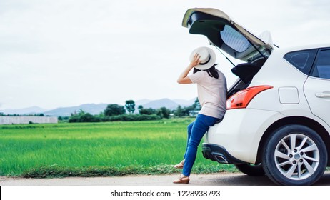 Young Woman traveler with hat sitting on hatchback car looking at mountain landscape against green grass field and cloudy sky. Woman travel alone in holiday concept.