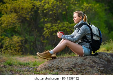 Young woman traveler hiking in summer forest and stopped to have rest with cup of tea. Travel, hiking, backpacking, tourism and people concept