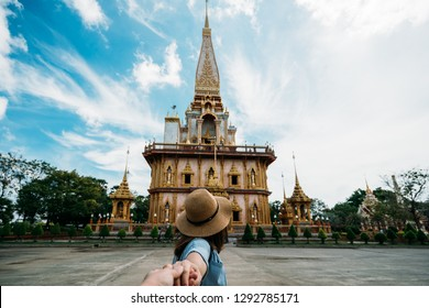Young woman traveler holding hand man into beautiful pagoda in Wat Chalong or Chalong temple at Phuket town, Thailand. It's most popular thai temple in Phuket Thailand.