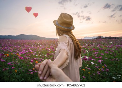 Young woman traveler holding man's hand and looking heart shape balloons flying in the sky on flowers field, Couple vacation travel concept