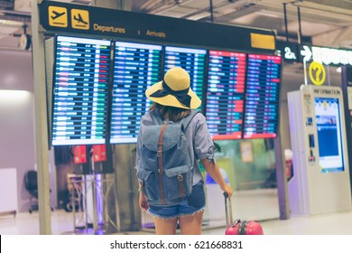 Young woman traveler in international airport looking at the flight information board holding suitcase or baggage in her hand, checking her flight at the airport terminal.