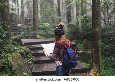 Young woman traveler looking map and walking in the nature education area in Xitou, Taiwan