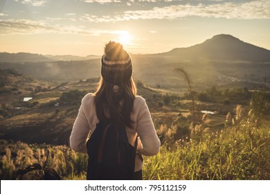 Young woman traveler looking at sunrise over the mountain with sunlight and flare