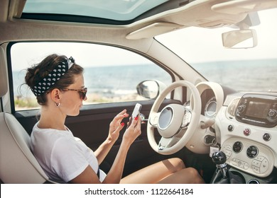 Young woman traveler on car using GPS navigator on her phone.