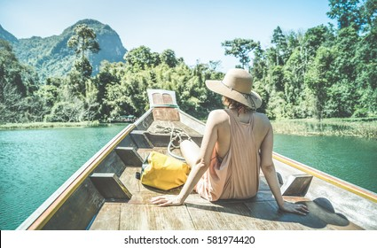 Young woman traveler on longtail boat trip at island hopping in Cheow Lan Lake - Wanderlust and travel concept with adventure girl tourist wanderer on excursion in Thailand - Retro turquoise filter