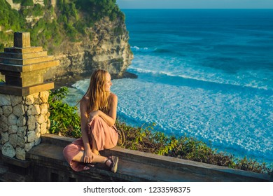 Young woman traveler in Pura Luhur Uluwatu temple, Bali, Indonesia. Amazing landscape - cliff with blue sky and sea