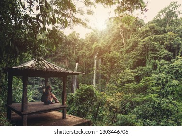 Young woman traveler seating in arbour on waterfall view point