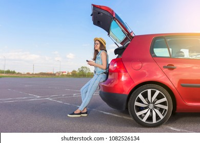 Young woman traveler sitting on hatchback car with outdoor sunny  background