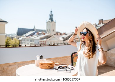 Young woman traveler sitting on the terrace enjoying great view on the old town of Lviv city in Ukraine