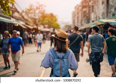 Young woman traveler with sky blue backpack and hat looking the way with in JJ Market in Bangkok Thailand. Traveling in Bangkok Thailand