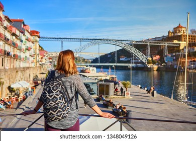 Young woman traveler standing back enjoying beautiful cityscape view on Douro river, bridge and boats during the morning light in Porto, Portugal