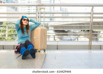 Young woman traveler suffering from a severe depression, anxiety/sudden fear, anxious of something with luggage