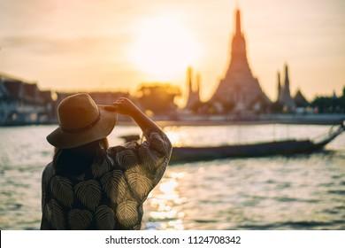 Young woman traveler traveling into Wat Arun Ratchawararam Ratchawaramahawihan Temple in bangkok, Thailand at sunset