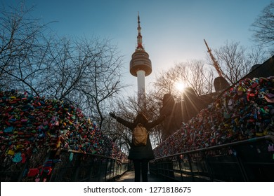 Young woman traveler traveling into the love key ceremony wall with happiness on N Seoul Tower at Namsan Mountain in Seoul City, South Korea.