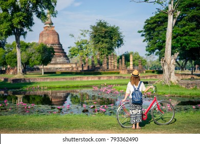 Young woman traveler travelling by bicycle into Wat Mahathat temple in the Sukhothai Historical Park contains the ruins of old Sukhothai, Thailand, UNESCO world Heritage Site.
