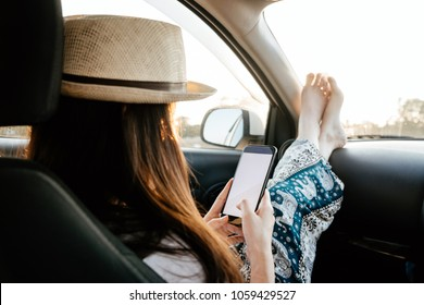 Young woman traveler using phone on car in sunset light.