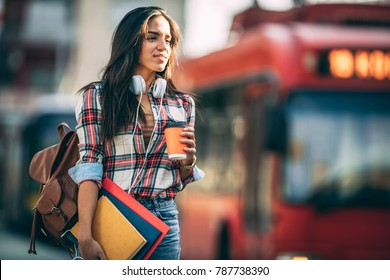 Young woman traveler waiting for a bus on a bus station, travel and active lifestyle concept