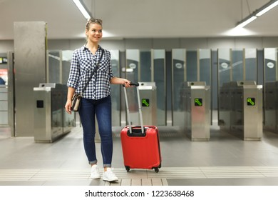 Young woman traveler walking in modern metro, carrying baggage