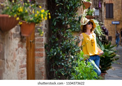 young woman traveler walking on narrow streets in Pienza, Tuscany, Italy