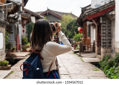 Young woman traveler walking and photographing at lijiang old town in Yunnan province, China