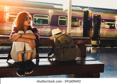 young woman traveler wearing backpack waiting railway at train station, Summer holiday and travel concept
