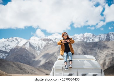 Young woman traveler in yellow jacket with heart shape enjoying beautiful mountain sitting on the car roof.