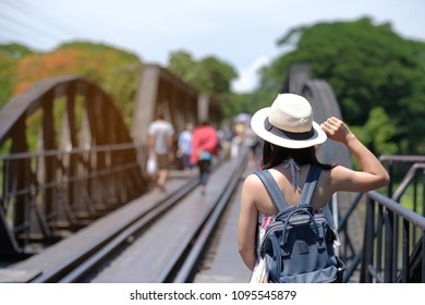 Young Woman traveling backpacker with hat, Asian traveler standing on the railway bridge over the river Kwai in Kanchanaburi, Thailand. history landmark and popular for tourist attractions