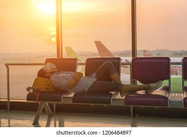 Young woman traveling by airplane. Tired passenger sleeping in airport terminal.
