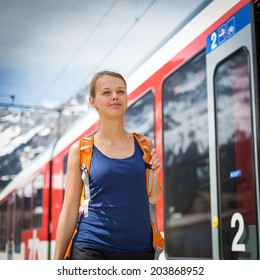 Young woman traveling by train, happy to have reached her destination