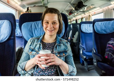 Young woman traveling by train while drinking a coffee