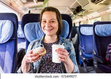 Young woman traveling by train while drinking a coffee - Shutterstock ID 571499077