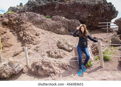 A young woman traveling in Europe and visiting the crater of volcano Vesuvius near town Pompeii in Italy in summer.