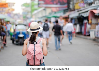 Young Woman traveling with hat, Asian hipster traveler walking at famous backpacker street in Bangkok (Khao San road), landmark and popular for tourist attractions in Thailand. Travel concept