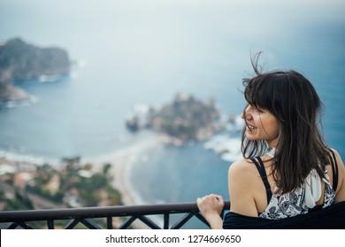 Young woman traveling to Italy.Visiting Taormina,Sicily,Italy.Woman traveler enjoying charming Mediterranean coastal city.Woman overlooking beaches  and crystal blue sea.
