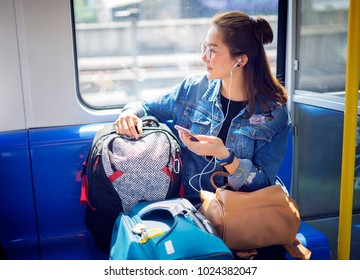 Young woman traveling looking out the window while sitting in the train. Enjoying travel. Young pretty woman with baggage traveling by Mass Rapid Transit(MRT)train near the window using smartphone.