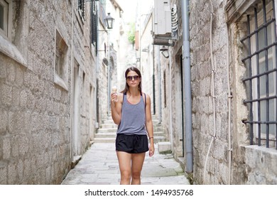 Young woman traveling, summer vacation, enjoying vegan ice cream, girl with sun glasses eating vegan ice-cream, sugar free, dairy free, outdoor, old city fortress in Kotor