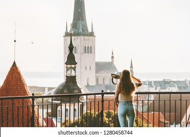Young woman traveling in Tallinn city vacations in Estonia weekend Lifestyle outdoor girl tourist sightseeing St Olav's Church Old Town architecture