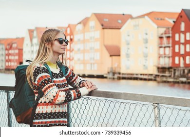 Young woman traveling in Trondheim city Norway vacations weekend Lifestyle fashion outdoor scandinavian houses landmarks architecture on background