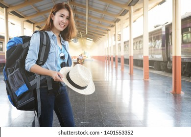Young woman traveller bag packing holding a hat and standing at train station. Travel concept.
